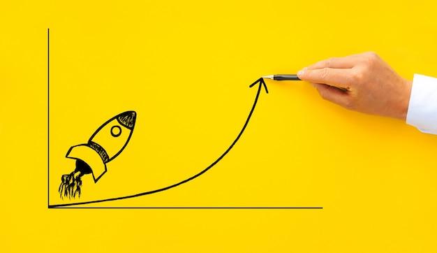 Empresário desenhando foguete inicial com crescimento de flecha Foto Premium