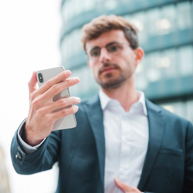 Empresário desfocado, olhando para o telefone móvel em pé na frente do edifício corporativo Foto gratuita