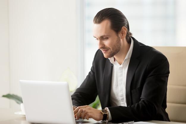 Empresário digitando no laptop na mesa no escritório Foto gratuita