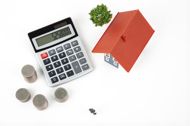 Empresário em miniatura e moedas com casa modelo Foto Premium
