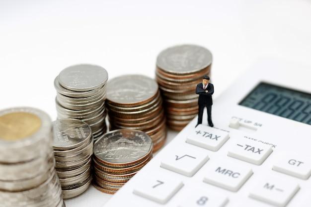 Empresário em miniatura na calculadora Foto Premium