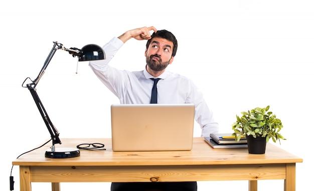 Empresário em seu escritório com dúvidas Foto gratuita