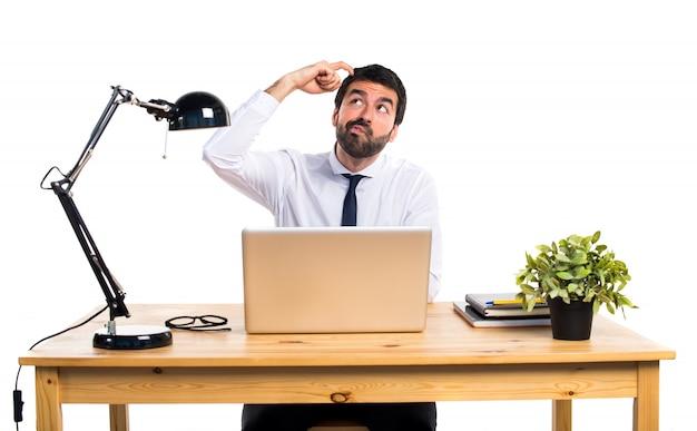 Empresário em seu escritório pensando Foto gratuita