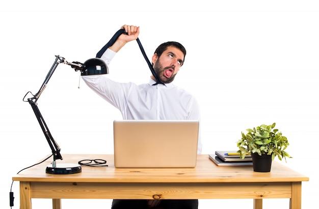 Empresário em seu escritório se afogando Foto gratuita