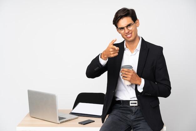 Empresário em seu escritório sobre parede branca aponta o dedo para você Foto Premium