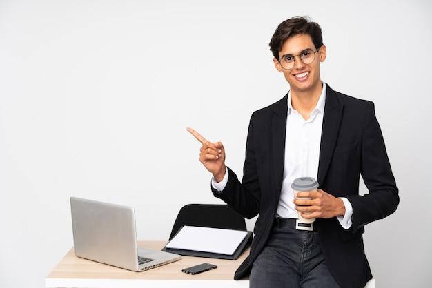 Empresário em seu escritório sobre parede branca isolada, apontando o dedo para o lado Foto Premium