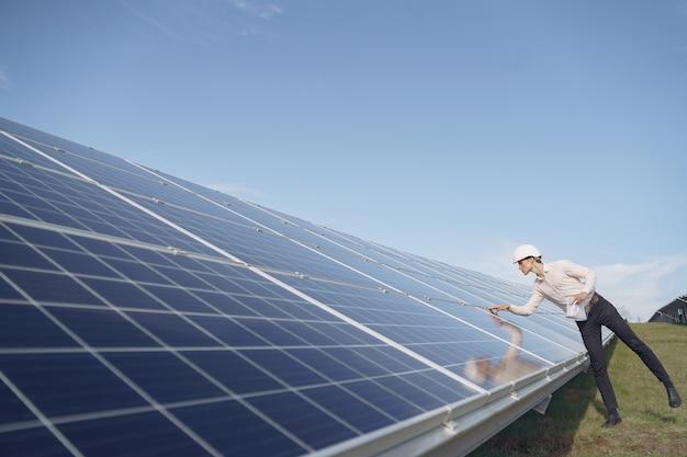 Empresário em um capacete branco perto da bateria solar Foto gratuita