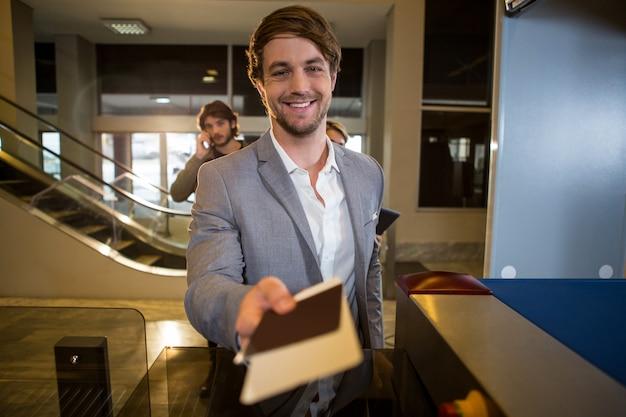 Empresário, entregando seu cartão de embarque no balcão Foto gratuita