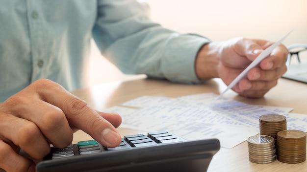Empresário está estressado com problemas financeiros, use uma calculadora para calcular o custo dos recibos colocados na mesa Foto Premium