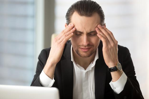 Empresário exausto, tendo uma dor de cabeça Foto gratuita