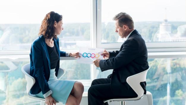 Empresário, explicando o gráfico ao seu colega do sexo feminino Foto gratuita