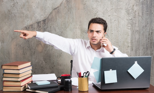 Empresário falando com telefone e apontando o lado dele na mesa do escritório. Foto gratuita
