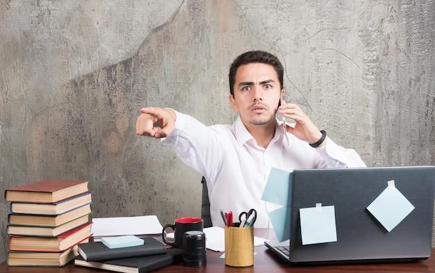 Empresário falando com telefone e apontando para a frente na mesa do escritório. Foto gratuita