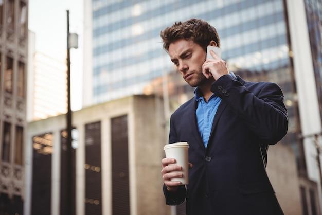 Empresário falando no celular e segurando café Foto gratuita