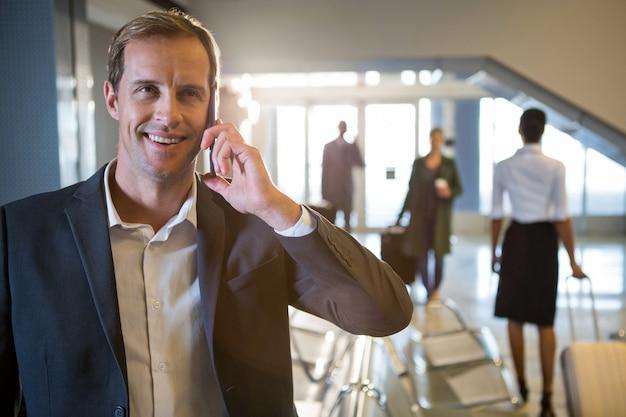 Empresário falando no celular na sala de espera Foto gratuita