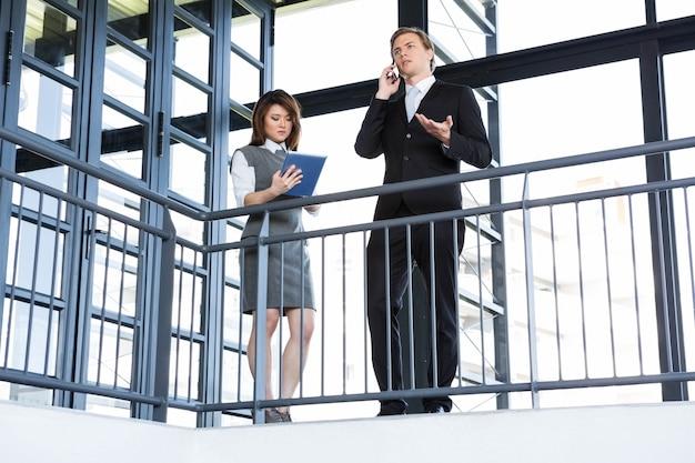 Empresário falando no smartphone e empresária usando tablet digital no escritório Foto Premium