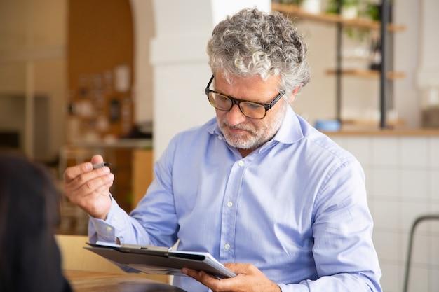 Empresário focado assinando acordo em reunião Foto gratuita