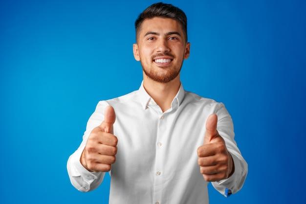 Empresário hispânico positivo mostrando o polegar para cima gesto Foto Premium