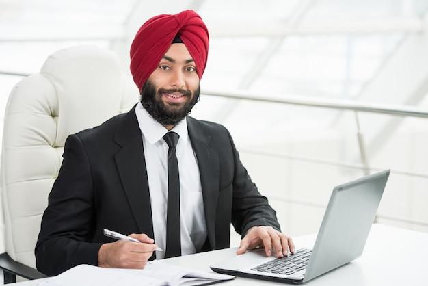 Empresário indiano confiante está trabalhando em seu computador. Foto Premium