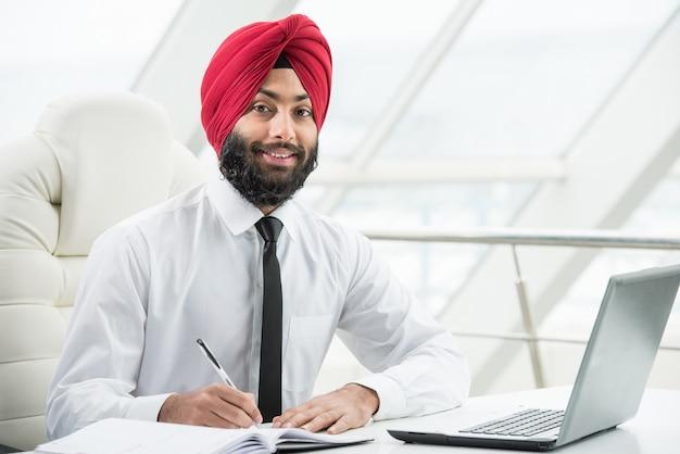 Empresário indiano está trabalhando em seu computador no escritório. Foto Premium