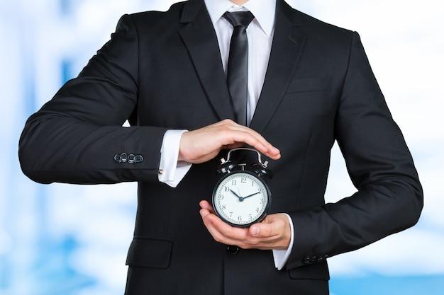 Empresário irreconhecível com um despertador em uma mão Foto Premium