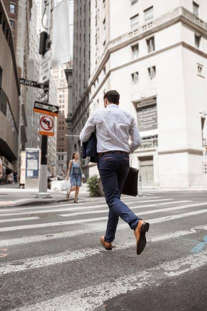 Empresário irreconhecível correndo na rua Foto gratuita
