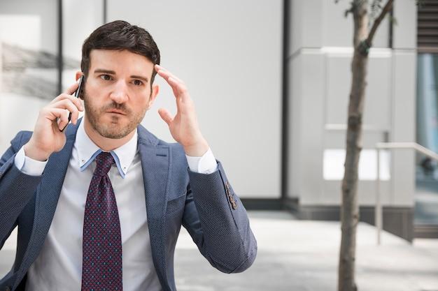 Empresário irritado falando no smartphone Foto gratuita