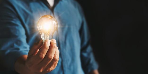 Empresário mão segurando a lâmpada. idéia alternativa de economia de energia Foto Premium