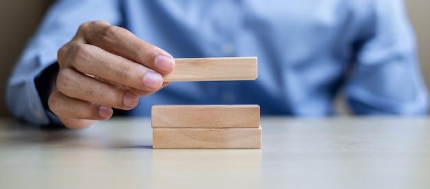Empresário mão segurando blocos de madeira na mesa Foto Premium