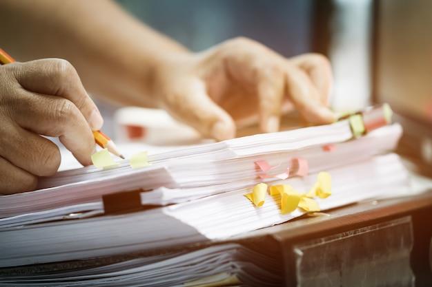 Empresário mãos segurando o lápis trabalhando em pilhas de arquivos em papel, procurando documentos inacabados atinge Foto Premium