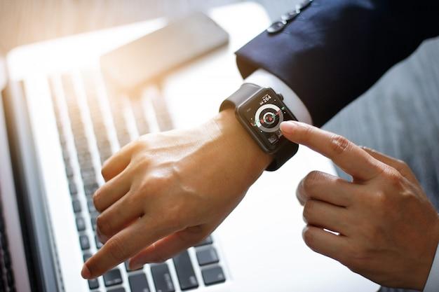Empresário mãos tocando relógio inteligente. usando um aplicativo do mercado de ações e gráfico na tela virtual moderna para os negócios. Foto Premium