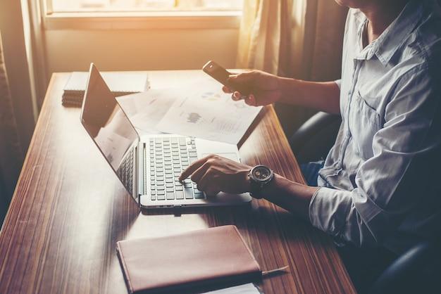 Empresário mãos usando telefone celular com laptop na mesa de escritório. Foto gratuita