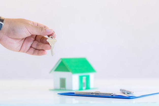 Empresário masculino segurando, dando as chaves da casa, close-up da mão, interior Foto gratuita