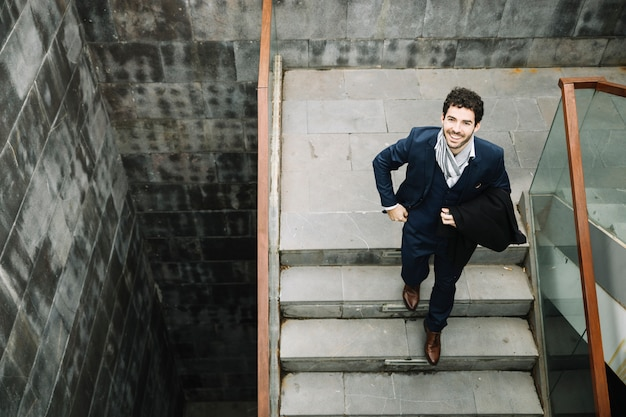 Empresário moderno e elegante, subindo as escadas Foto gratuita