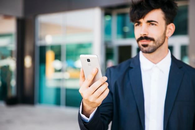 Empresário moderno olhando para o smartphone Foto gratuita