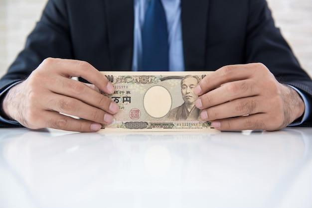 Empresário mostrando notas de dinheiro em ienes japoneses em cima da mesa Foto Premium