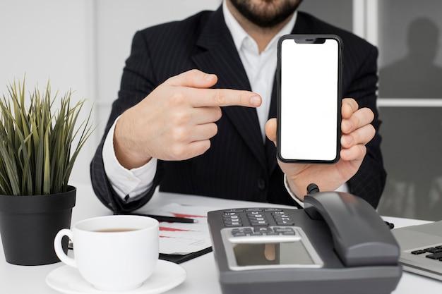 Empresário mostrando telefone celular Foto gratuita