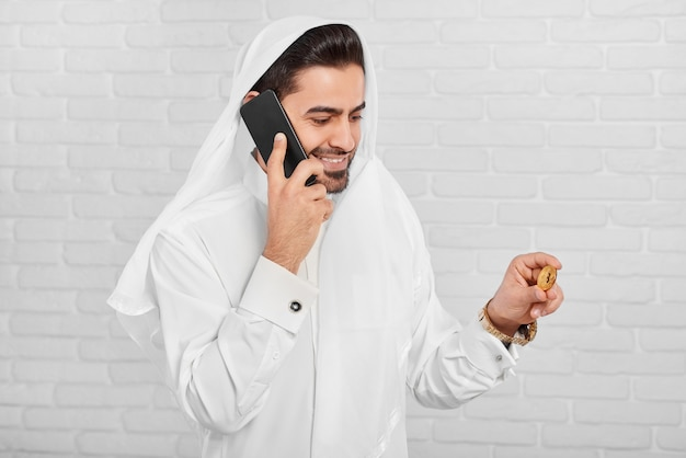 Empresário muçulmano em trajes tradicionais mantém bitcoin e fala ao telefone Foto Premium