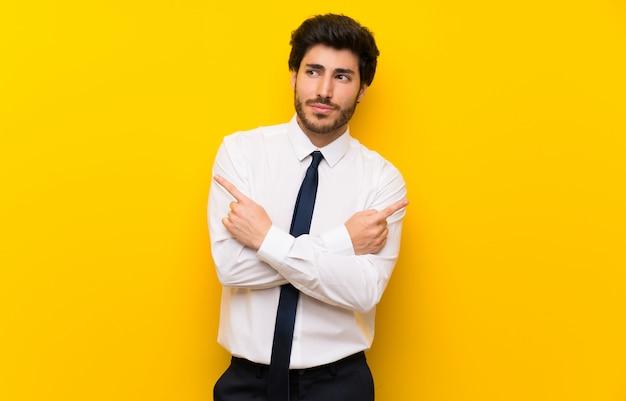 Empresário na parede amarela isolada, apontando para as laterais, tendo dúvidas Foto Premium
