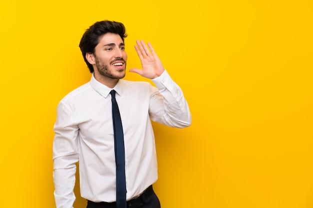Empresário na parede amarela isolada, gritando com a boca aberta Foto Premium