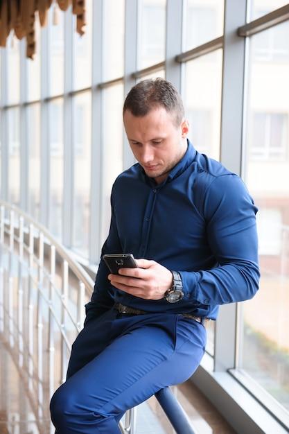 Empresário, olhando através do telefone pela janela Foto Premium