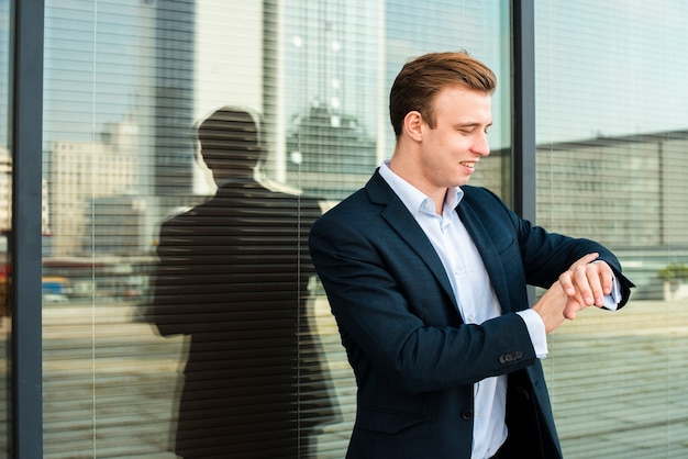 Empresário, olhando para o relógio de pulso Foto gratuita