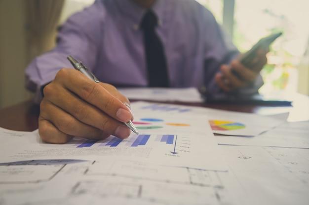 Empresário ou contador trabalhando na calculadora para calcular o conceito de dados comerciais. Foto Premium