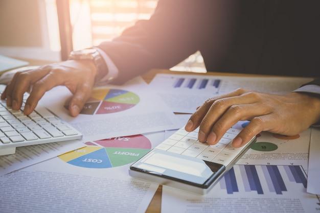 Empresário ou contador trabalhando na calculadora para calcular o conceito de dados de negócios Foto Premium