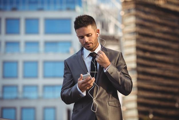 Empresário, ouvindo música no celular Foto gratuita
