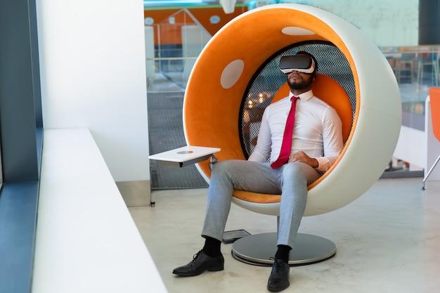 Empresário pacífico no fone de ouvido vr desfrutando de vídeo virtual Foto gratuita