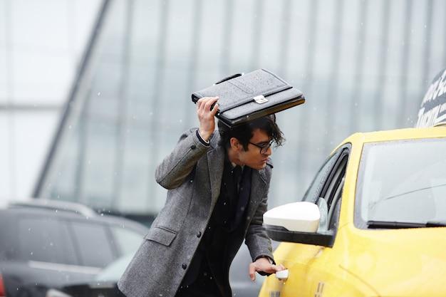 Empresário pegando táxi na tempestade Foto gratuita