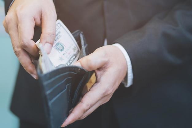 Empresário pessoa segurando uma carteira nas mãos de um homem tirar dinheiro do bolso. Foto Premium
