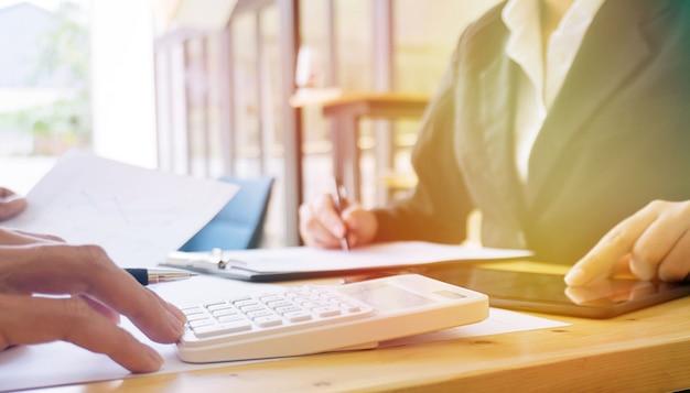 Empresário que analisa gráficos de investimentos e pressiona os botões da calculadora em documentos. conceito de contabilidade Foto Premium