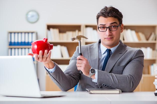 Empresário quebrando piggybank no escritório Foto Premium